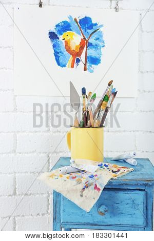 Metal mug with brushes and palette knives on small table