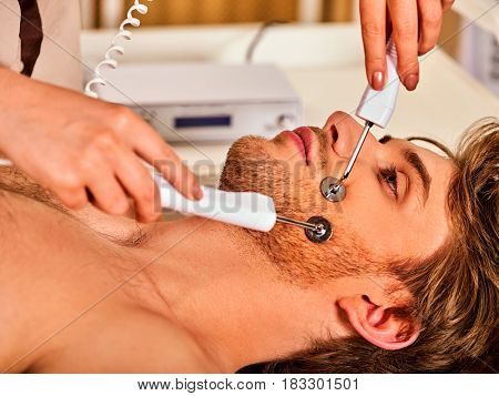 Facial massage at beauty salon. Electric stimulation skin care of man. Equipment for microcurrent lift face. Anti aging face and neck and close up rejuvenation and non surgical treatment indoor.