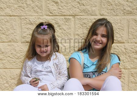 two sisters pose in front of yellow wall
