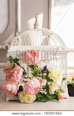 Shabby chic decoration with beautiful vintage birdcage and flowers.