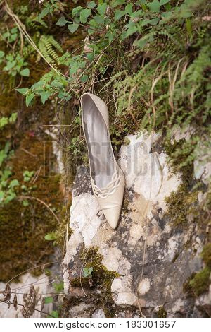 Elegant shoe of the bride attached to a rock wall