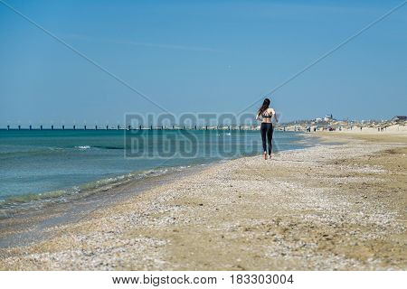 Beautiful young woman Jogging on the beach, rear view.