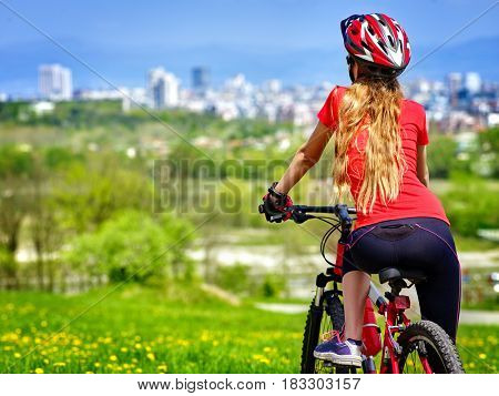 Bicycle girl has rest. Woman wearing sport helmet rides returns into city. Cycling is good for health. Cyclist is looking at city in distance.