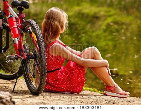 Bicycle girl wearing red polka dots dress admires pond into park. Woman sitting on green grass near water in summer park.