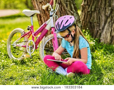 Child traveling bicycle in summer park. Bicyclist little girl watch on tablet computer. Kid in helmet counts pulse after sport training and is looking for way to navigator.