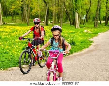 Mother and daughter on bicycle. Bikes cycling family. Happy mother teaching daughter to ride bike . Kid practice to riding lady bicycle.