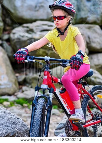 Child on bicycle ride mountain. Girl traveling in summer park. Cycling person wearing helmet . Sport trip is good for children health.