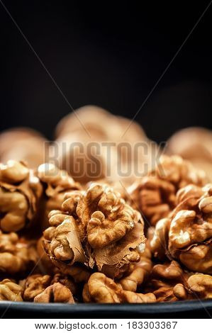 Walnuts. Nuts of walnuts. Nuts in black plates against the background of a black wooden background. Rustic. Fresh autumn walnut harvest in the village. Place for text