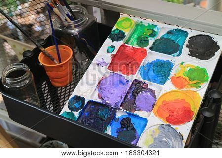 Modern style art palette with multi-color paints on a black tool cart