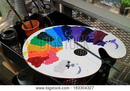 White art palette with multi-color paints and paintbrush on black tool cart