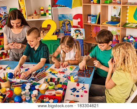 Small students with teacher painting in art school class. Child drawing by paints on table. Craft drawing education develops creative abilities of children. Collective children's creativity.