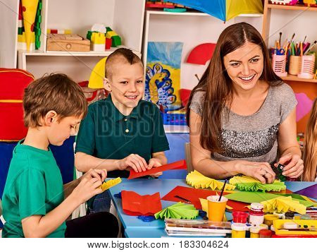 Preschool scissors in kids hands cutting paper with teacher in class room. Development and social lerning happy children in school. Children's project in kindergarten. Small group girls together.