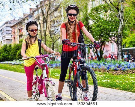 Bicycle path with children. Girls wearing bicycle helmet with rucksack ciclyng ride. Kids or mother with daughter are on yellow bike lane . Alternative to urban transport. Flowerbed with flowers in