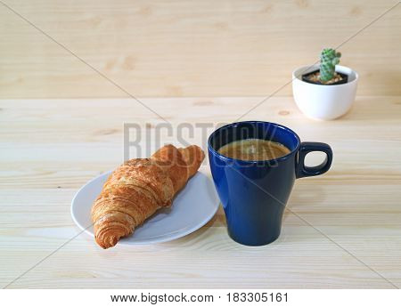 Coffee and Whole Wheat Croissant on the Wooden Table with a Mini Cactus Plants