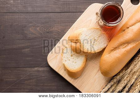 Rustic bread or baguette with honey on the wooden background.