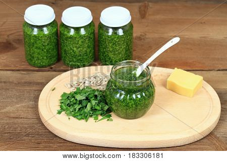 Homemade pesto in jars on rustic wooden board. Made from wild garlic olive oil parmesan cheese and nuts.