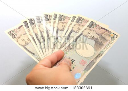 Hand Hold A 10000 Japanese Currency, Bill Yen In A Crocodile Texture Wallet,on White Background, A C