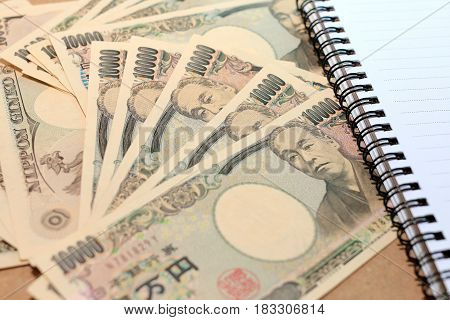 10000 Japanese Yen Note With On Japanese Yen Currency With Notebook.