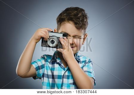 child taking a picture using a retro rangefinder camera isolated grey background.