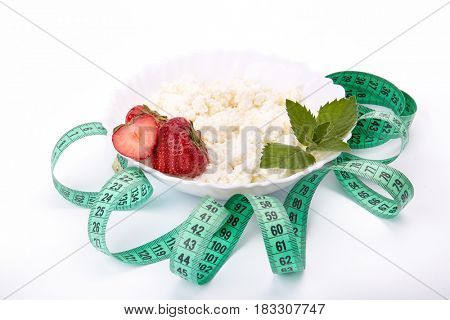 Natural cottage cheese with fresh ripe strawberries, leaf of mint and measuring tape on a white background. Healthy eating concept. Dieting and slimming.