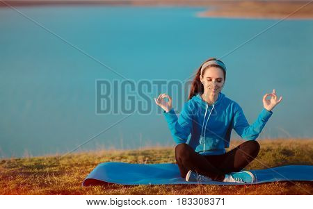 Happy Girl Meditating on Yoga Mat in Nature