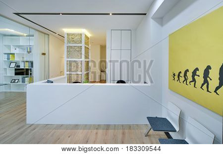 Office in a modern style with white walls and a parquet on the floor. There is a reception desk, chairs, brick column with backlighting, work zone with a glass partition and a door, glowing lamps.