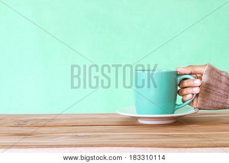hand holding Coffee cup mug on wooden table Romance and love background . Happy and relax concept