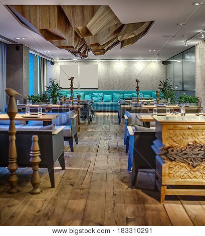 Cafe in a modern style with textured walls. There are sofas with pillows, tables, chairs, wooden poles with birds, plants, commode with ornament. On the ceiling there is wooden geometric construction.