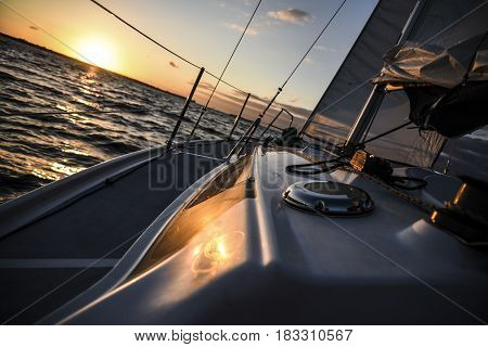Sailboat in open sea at sunset, summer time