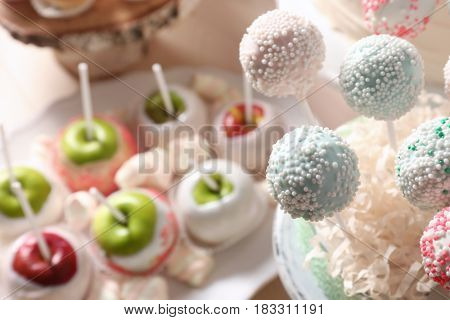 Stand with tasty cake pops prepared for party, on blurred background