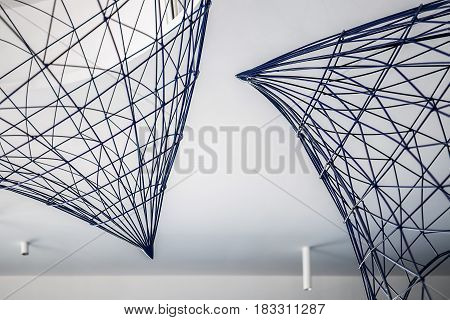 Reticulated metal constructions on the white ceiling background. Closeup. Horizontal.