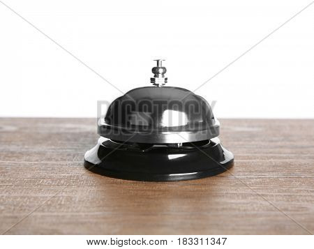 Silver service bell on wooden table against white background