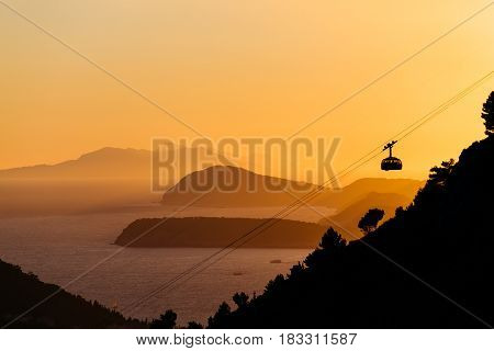 Cableway or ropeway to the mountain Srdj in Dubrovnik, Croatia against the background of a sunset over the islands in the sea