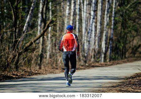 middle-aged man running asphalt road in spring park