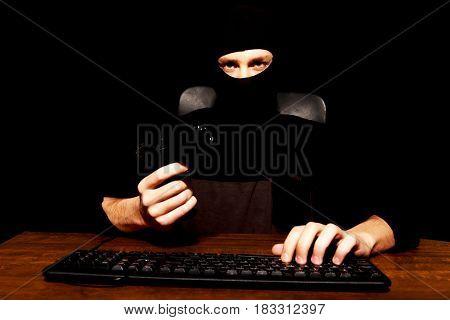 Dangerous hacker in balaclava holding gun