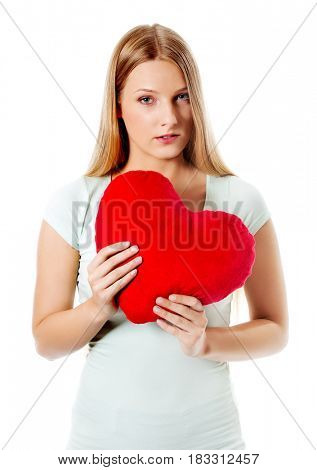 Young woman with a heart pillow in her hands - Valentines day concept.