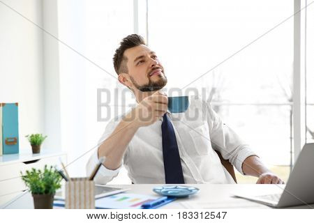 Happy young man resting and drinking coffee in office