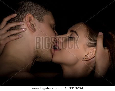 Close-up young love couple kissing on a dark background.