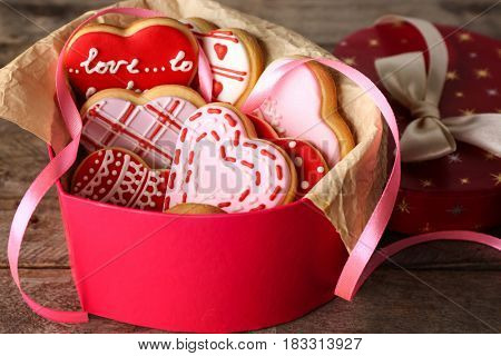 Heart shaped box with cookies for Valentine's day on wooden background