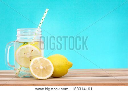 Citrus lemonade water with lemon sliced healthy and detox water drink in summer on wooden table with blue lighten background