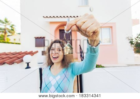 Young woman In Front of New Home with New House Keys.