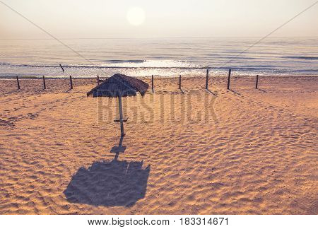 sun rising over calm sea and empty beach