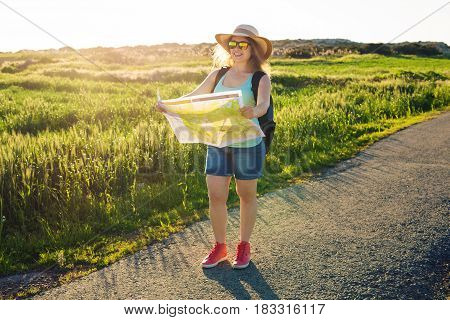 Tourism, travel and summer concept - Happy woman traveler with backpack checks map to find directions