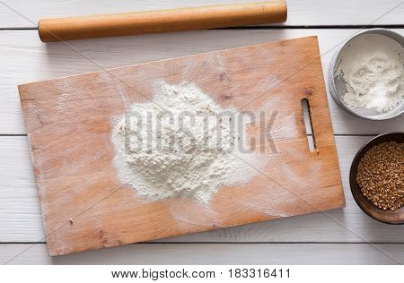 Baking class or recipe concept on white background, sprinkled wheat flour and seeds on wooden board on table. Cooking dough or pastry.