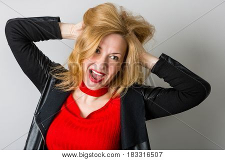 Expressive woman in a black jacket against a wall background. Woman is forty years old.