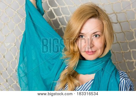 Beautiful woman in blue on the background of a fishing net. Woman is forty years old.
