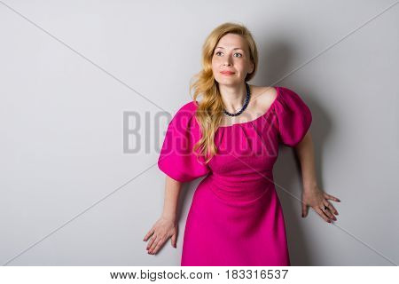 Beautiful woman in a pink dress near a gray wall. Woman is forty years old.
