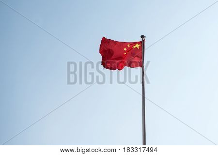 The Chinese Flag Flies In The Blue Sky.