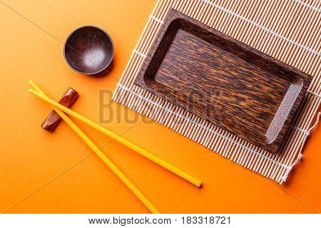 Photo of sticks for sushi, plates on empty orange background