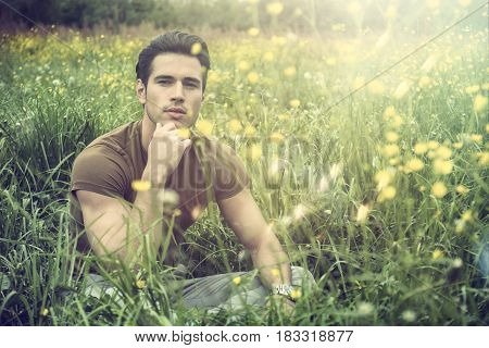 Attractive, fit young man relaxing sitting on lawn in the countryside among grass, looking at camera, smiling